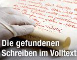 """Schriftstück, gezeichnet von """"Alfons Riedel, Bildhauer"""", wird ausgerollt"""