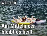 Zwei Junge Frauen schwimmen mit einer Luftmatraze im See