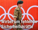 Soldat geht an einem Plakat mit den Olympischen Ringen vorbei