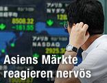 Asiatischer Aktienhändler vor einer Anzeigentafel