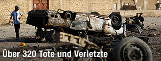 Passanten neben ausgebrannten Autowracks im Irak
