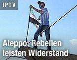 Vermummter syrischer Rebell mit Fahne auf einem Hausdach