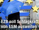 Frau geht mit Euro-Rettungsschirm vor der Europäischen Zentralbank