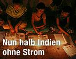 Jugendliche sitzen in Delhi am Boden und lesen bei Kerzenschein