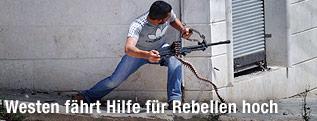 Mitglied der Freien Syrischen Armee mit Maschinengewehr an einer Hausecke