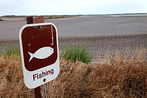 """Schild mit der Aufschrift """"Fishing"""" neben einem ausgetrockneten See"""