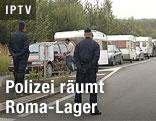 Polizei steht neben Karawane aus Wohnwagen