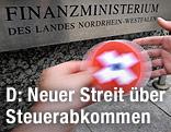 Eine Hand gibt einer anderen vor dem Finanzministerium von Nordrhein-Westfalen eine CD mit Schweizer Flagge