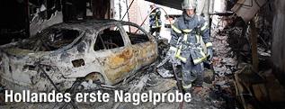 Feuerwehrmann neben einem ausgebrannten Autowrack