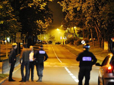 Französische Polizisten beobachten die Krawalle von der Distanz aus