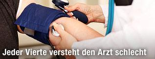 Arzt beim Blutdruck messen