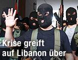 Maskierte Männer mit Waffen