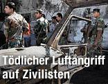 Syrische Soldaten neben einem ausgebrannten Auto