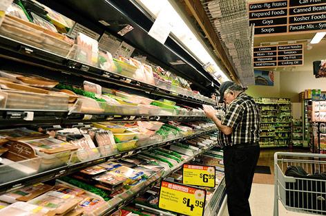Ein Mann steht in einem amerikanischen Supermarkt vor dem Kühlregal mit Fleischwaren