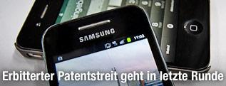 Ein Samsung-Smartphone liegt auf einem iPhone von Apple