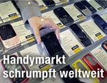 Eine Verkäuferin nimmt ein Smartphone aus dem Sortiment