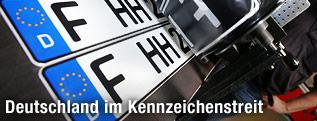 Ein Autokennzeichen läuft aus der Druckmaschine beim TÜV in Frankfurt am Main
