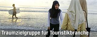 Muslimische Frauen am Strand und ein Surfer im Hintergrund
