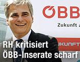 Bundeskanzler Werner Faymann im Jahr 2007 neben einem ÖBB-Logo