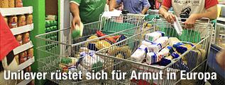 Hände legen in einem Supermarkt Produkte in einen Einkaufswagen