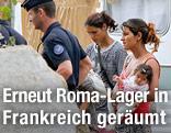 Zwei Frauen mit Kleinkind werden von zwei Polizisten von ihrem Wohnwagen abgeführt