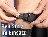 Hände montieren elektronische Fußfessel an einem Bein