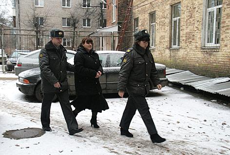 Die russische Aktivistin Taissja Ossipowa wird von Polizei zu einem Verhandlungstermin in einem Gericht begleitet