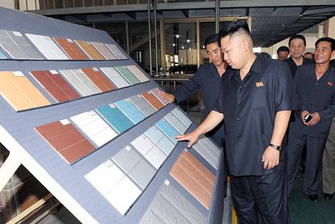 Kim Jong Un betrachtet Dachziegel in einer Fabrik