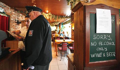 Ein Polizist kontrolliert eine Bar