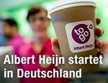 """Angestellte des Minimarktes """"Albert Heijn to go"""" mit Kaffeebecher"""