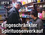 Polizist kontrolliert die Waren in einem Spirituosengeschäft