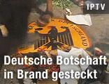 Demonstranten treten auf Schild der deutschen Botschaft ein
