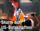 Mann vor einem Feuer vor der deutschen Botschaft in Khartum