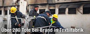 Feuerwehrleute vor dem ausgebrannten Fabriksgebäude