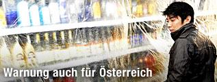Ein Verkäufer verhüllt ein Regal mit hartem Alkohol mit durchsichtigem Plastik