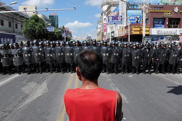 Demonstrant steht vor Mauer aus Sicherheitskräften