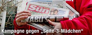 Kolporteur hält eine Ausgabe der englischen Boulevardzeitung The Sun in der Hand