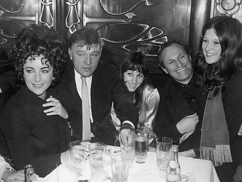 Elizabeth Taylor, Richard Burton,Vicky Tiel, Louis Feraud und Mia Fonssagrives sitzen in einem Lokal an einem Tisch