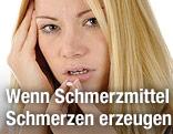 Frau mit Kopfschmerzen schluckt Tablette
