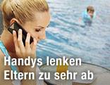 Frau telefoniert am Handy, Kind schwimmt im Swimmingpool im Hintergrund