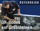Mann steht neben Grabstein mit QR-Codes