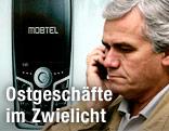 Mann mit Handy vor einer Werbung der Firma Mobtel