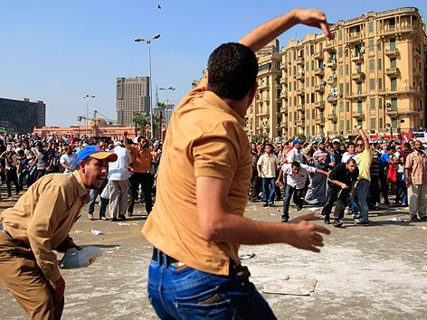 Ein Mann wirft auf dem Kairoer Tahrirplatz einen Stein auf Demonstranten