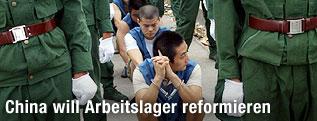 Verurteilte flankiert von chinesischen Polizisten