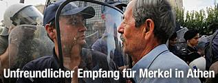 Älterer grichischer Demonstrant Aug in Aug mit einem Polizisten