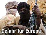 Islamistischer Kämpfer vermummt, mit Feuerwaffe in der Hand