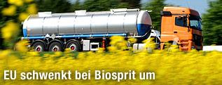 Ein Tanklastzug fährt an einem Rapsfeld vorbei