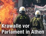 Flammen vor Einsatzkräften des Sonderkommandos, dahinter Demonstranten