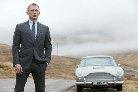 """Szene aus dem neuen James Bond """"Skyfall"""", James Bond steht vor einem alten Aston Martin"""