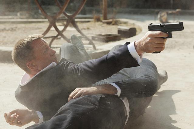 """Szene aus dem neuen James Bond """"Skyfall"""", James Bond liegt vor einem Toten und schießt mit seiner Waffe"""